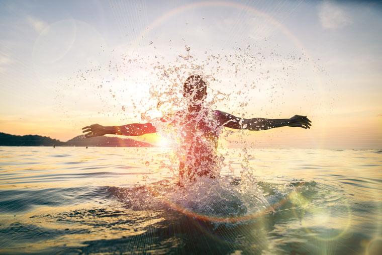 Mann t aucht aus Wasser auf